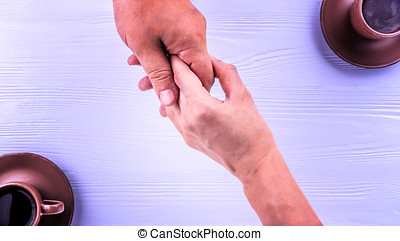 Man and woman hands holding each other with a cups of coffee on the background. Care concept.