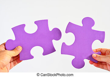 Man and woman hands holds two different puzzle pieces...