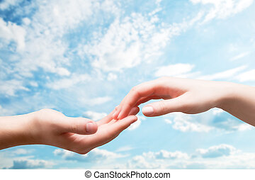 Man and woman hands touch in gentle, soft way on blue sunny sky