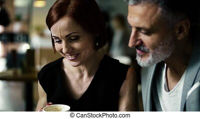 Man and woman having business meeting in a cafe, talking.