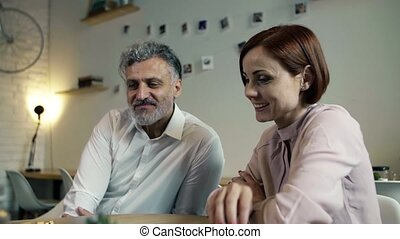 Man and woman having business meeting in a cafe, using...
