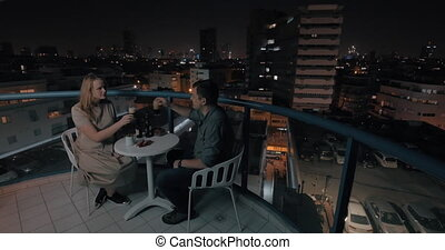 Man and woman having drinks on the rooftop cafe in night city