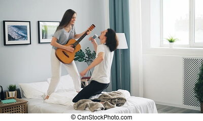 Man and woman having fun playing guitar singing in remote control dancing on bed