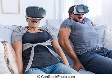 Man and woman having fun with a VR glasses