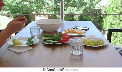 man and woman having outside light lunch on the balcony