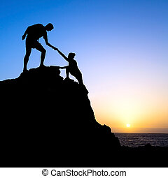 Couple hiking help each other silhouette in mountains, sunset and ocean. Male and woman hiker helping each other on top of mountain climbing, beautiful sunset landscape.