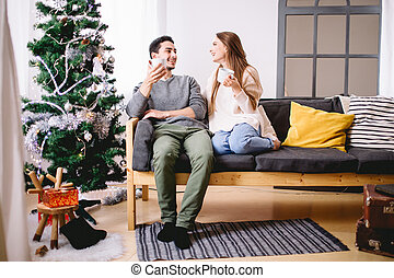 Man and woman hold cups of hot drink sitting before white Christmas tree
