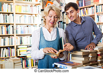 Man and woman holding books - ?heerful young man and mature ...