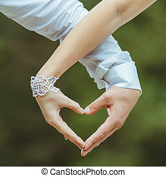 Man and woman holding by hands and making love heart -...