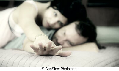 Man and woman holding hand in bed