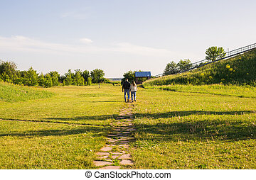 Man and woman holding hands and walking on country road, back view
