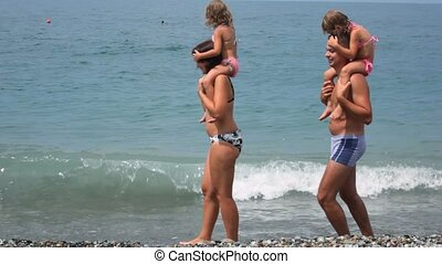 man and woman holding little girls on shoulders walks on beach with sea surf