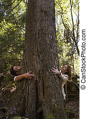 Man and woman hugging a tree