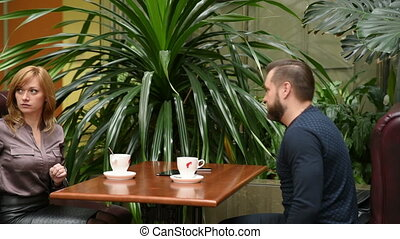 man and woman in a cafe called the waiter.
