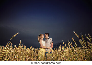 man and woman in a wheat field against the sky