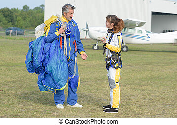 Man and woman in airodrome holding parachute