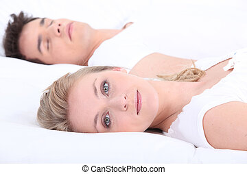Man and woman in bed with eyes open