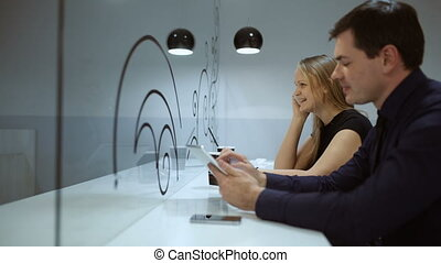 Man and woman in cafe busy with phone and pad