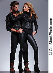 man and woman in fashionable leather clothes looking at each