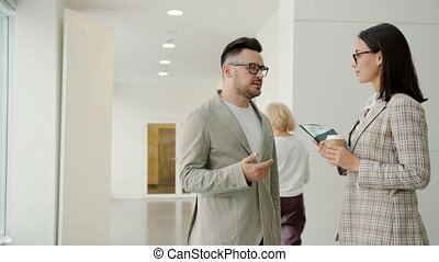 Man and woman in formalwear talking in office lobby while ...