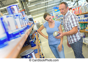 Man and woman in hardware store, holding tin