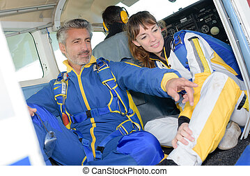 Man and woman in jumpsuits in aircraft