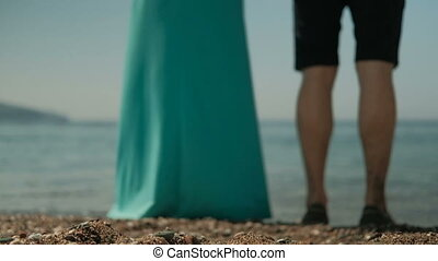 Man and woman in long dress holding hands standing on the beach. They hold hands
