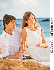 Man and Woman in love, Couple enjoying glass of champagne on tropical beach at sunset, Honeymoon concept