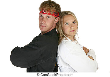 Man and woman in martial arts uniforms back to back