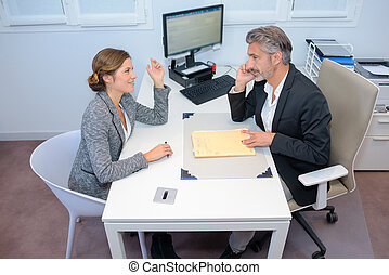 Man and woman in meeting at office table