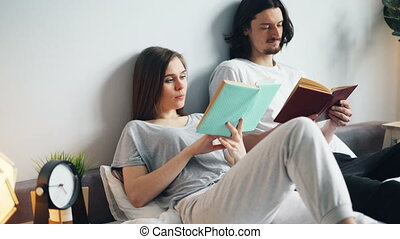 Man and woman in pajamas reading books in bed at home...