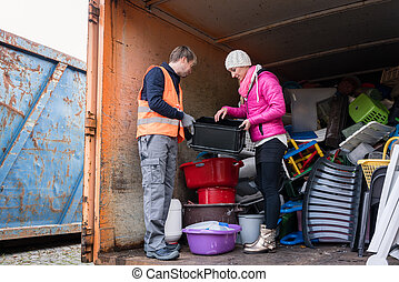 Man and woman in recycling center standing in container