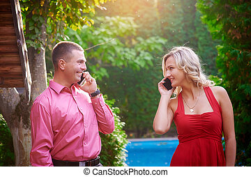 man and woman in red dress talking on the phone with each other