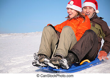 man and woman in santa claus hats ride on sled
