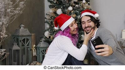 New Year, Christmas, Xmas, holiday and celebration concept. Young man and woman in Santa's hats are doing selfie on smartphone near Christmas tree. Happy smiling husband and wife together.