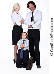 Man and woman in smart suit and little boy dressed as a businessman