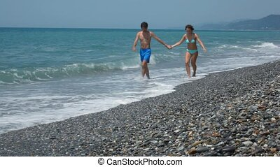 man and woman in swimsuit having joined hands walking on sea coast to camera