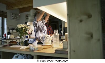 Man and woman in the kitchen, preparing drinks, normal day