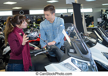 Man and woman in vehicle showroom
