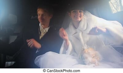 man and woman in wedding dresses sit in limousine together,...