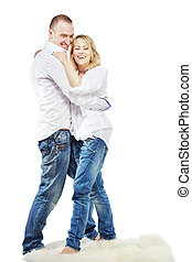 Man and woman in white shirts and blue jeans dance and laugh on the white carpet.