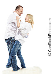 Man and woman in white shirts and blue jeans dance on the white carpet.