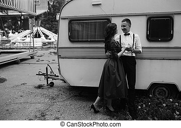 man and woman is hidden from view behind a trailer