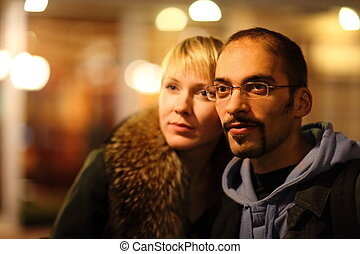 man and woman is pasearing in coldly night city. focus on man's face.