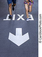 Man and woman jogging together on street with exit sign