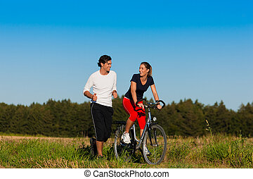Young fitness couple doing sport outdoors, jogging and riding a bicycle in autumn under a clear blue sky