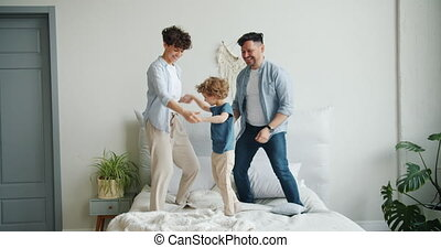 Man and woman jumping dancing on bed with happy child having...