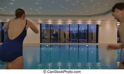 Man and woman jumping into the indoor swimming pool