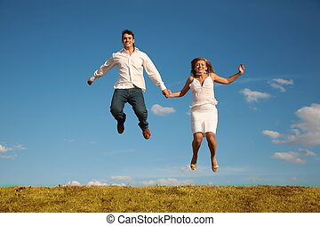 man and woman jumping on the meadow