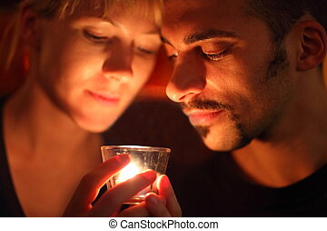 man and woman keeping glass candle and looking at it. focus ...